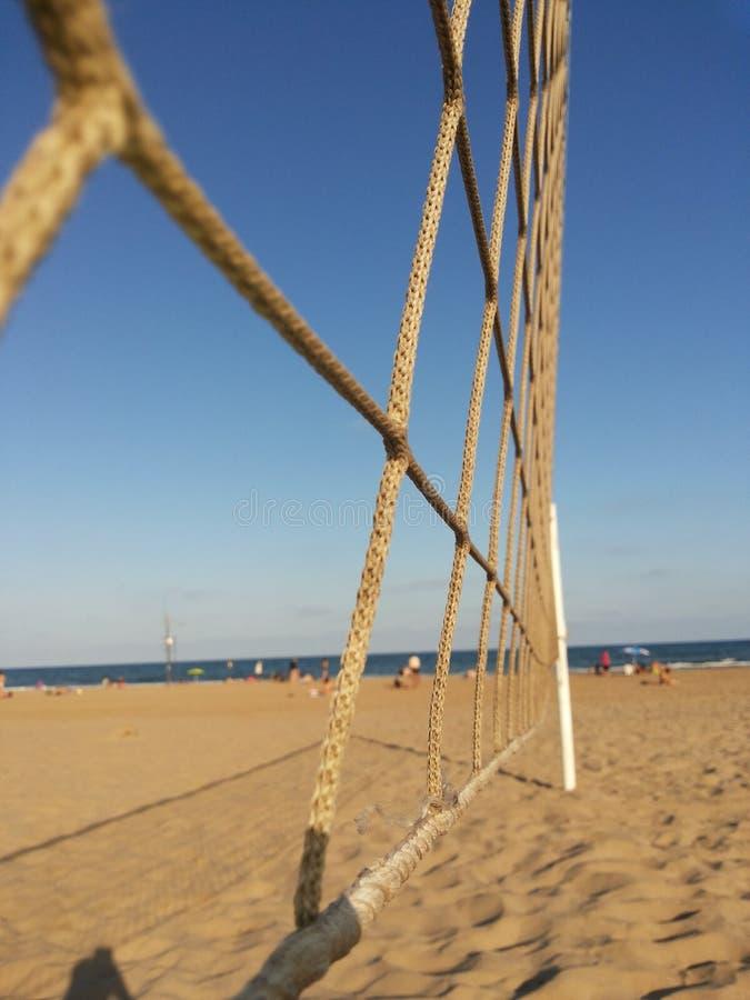 Volleyballnetz auf dem Strand durch das Meer stockfotografie