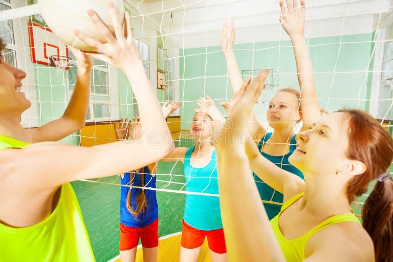 Volleyballspel tussen tienerteams in gymnasium stock afbeelding