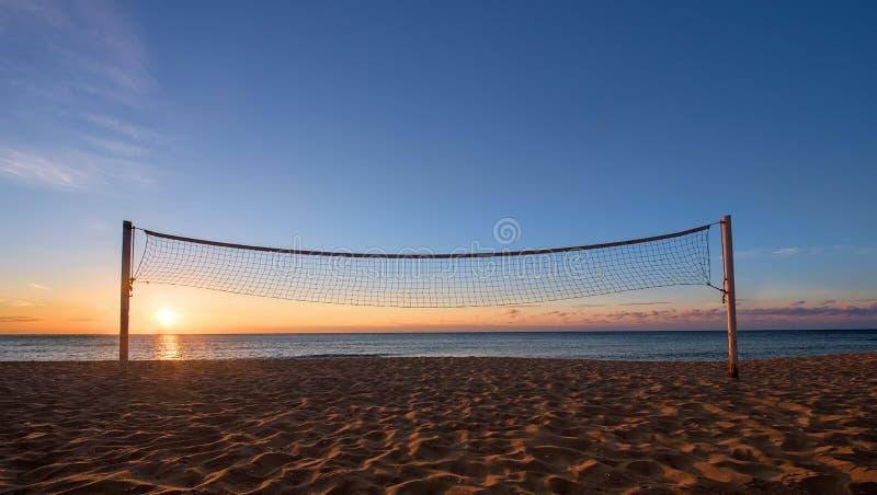 Volleyboll förtjänar mot soluppgång på stranden royaltyfri foto