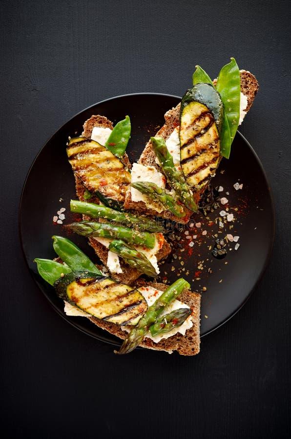 Vollkornbrotsandwiche mit Feta, gegrillte Zucchini, grüner Spargel, Zuckererbsen, Olivenöl auf einem schwarzen Hintergrund lizenzfreie stockbilder