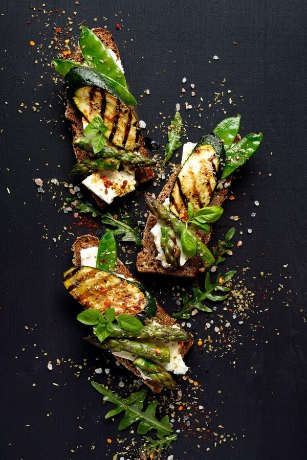Vollkornbrotsandwiche mit Feta, gegrillte Zucchini, grüner Spargel, Zuckererbsen, Olivenöl auf einem schwarzen Hintergrund stockbild