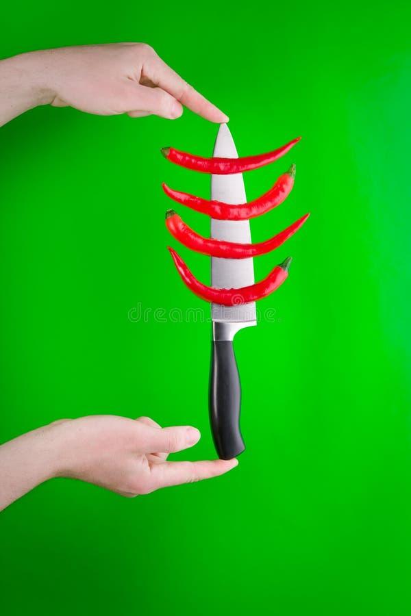 Vollständige rote Pfeffer auf Messer lizenzfreie stockfotografie