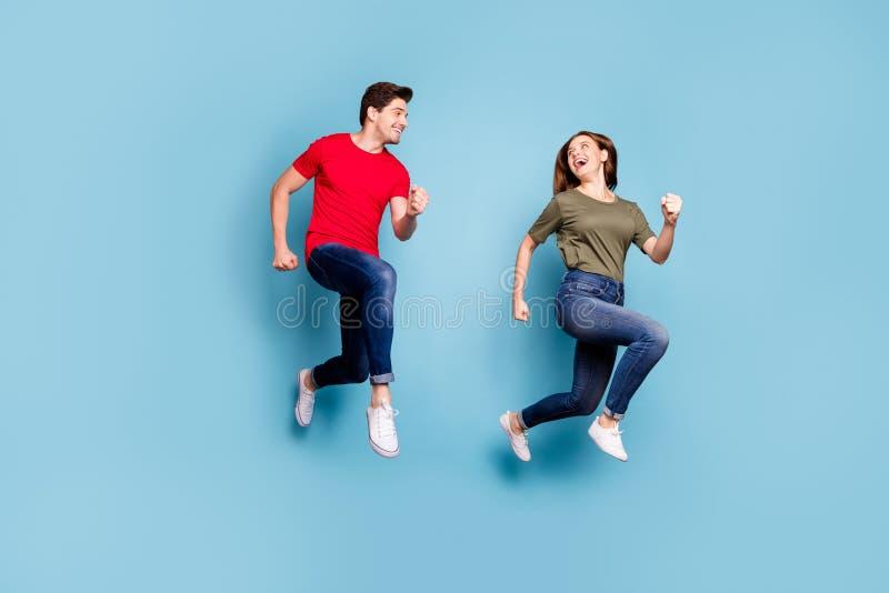 Vollständiges Foto von charmanten Ehepartnern entspannen Ruhepause Laufen tragen grüne rote T-Shirt denim Jeans Sneakers isoliert stockbilder