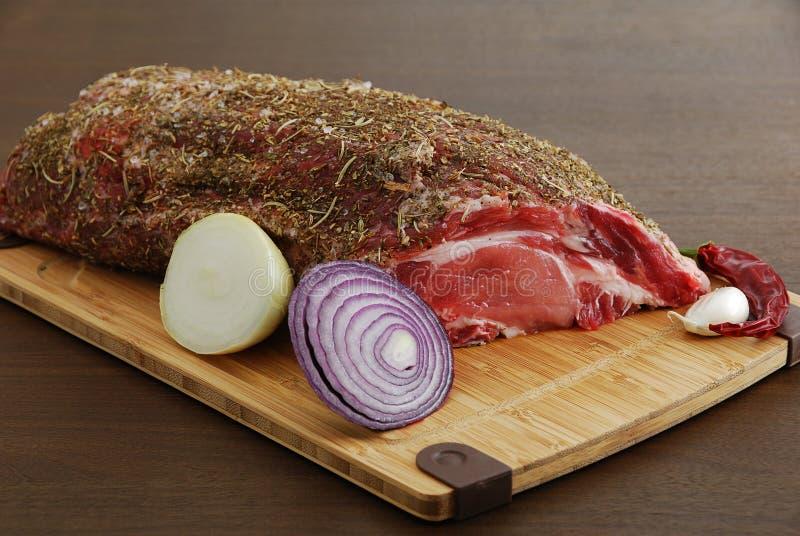 Vollständiges Stück rohes Fleisch mit Gewürzen stockbild