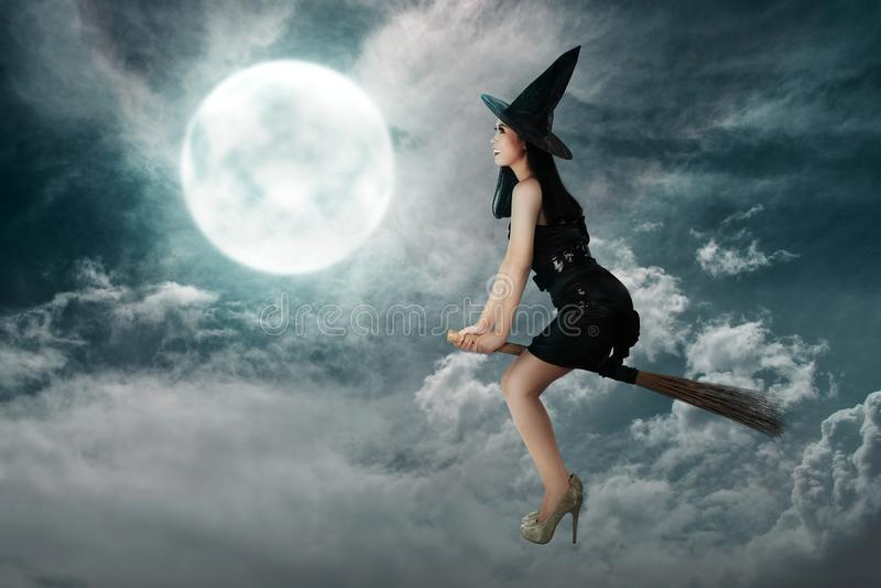 Volo asiatico felice della donna della strega sopra un manico di scopa fotografie stock