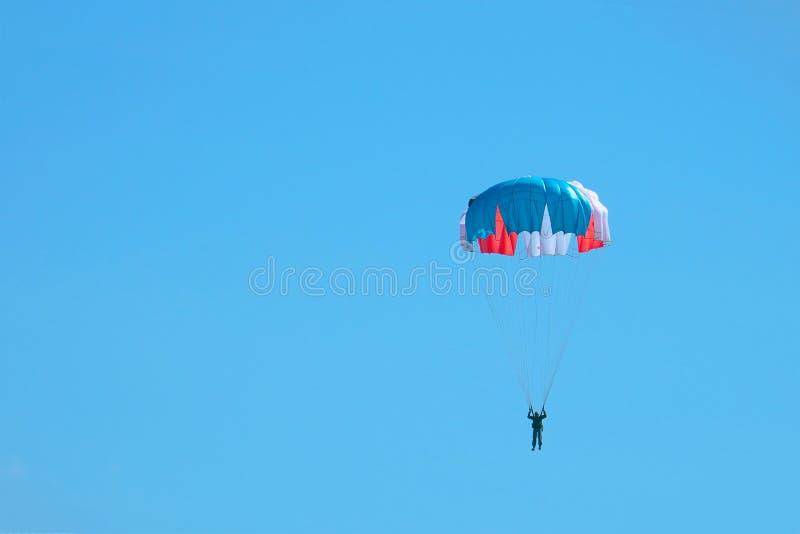 Volo del paracadutista nel blu in cielo immagini stock