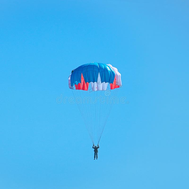 Volo del paracadutista nel blu in cielo fotografia stock