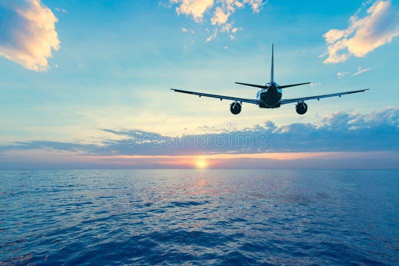 Volo del piano passeggeri sopra la superficie del mare fotografie stock libere da diritti