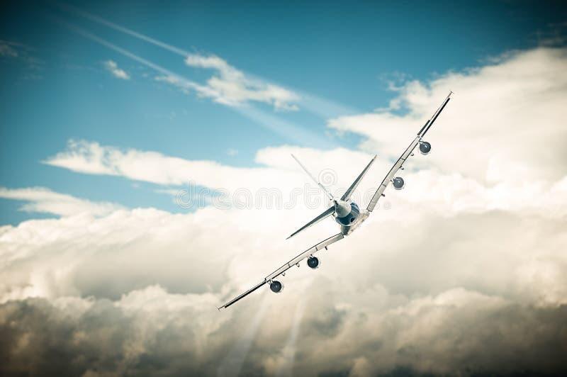 Volo dell'aereo bianco in cielo blu sopra le nuvole. fotografia stock