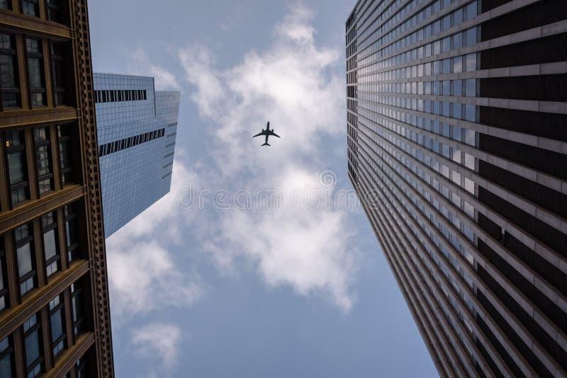 Volo dell'aeroplano sopraelevato in Chicago del centro in mezzo a due costruzioni fotografia stock libera da diritti