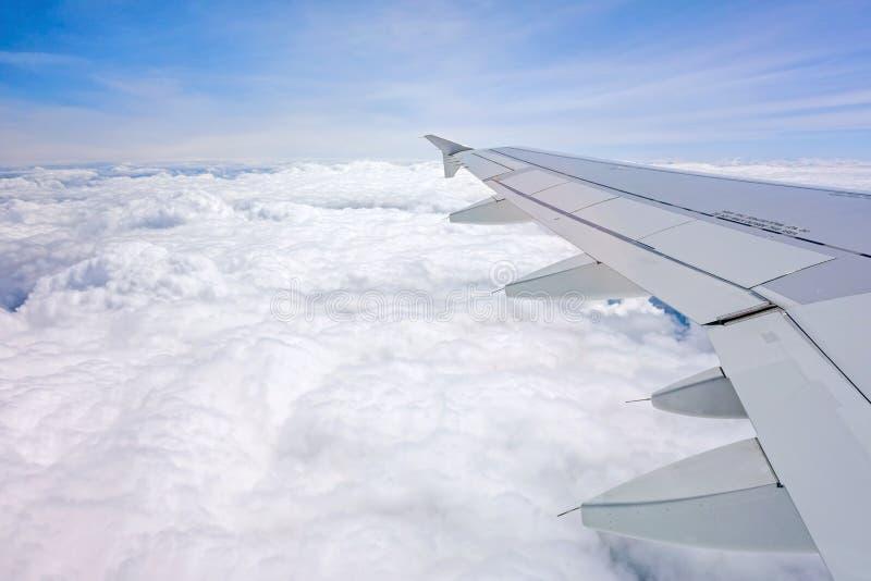 Volo dell'aeroplano - vista della finestra sopra le nuvole fotografia stock