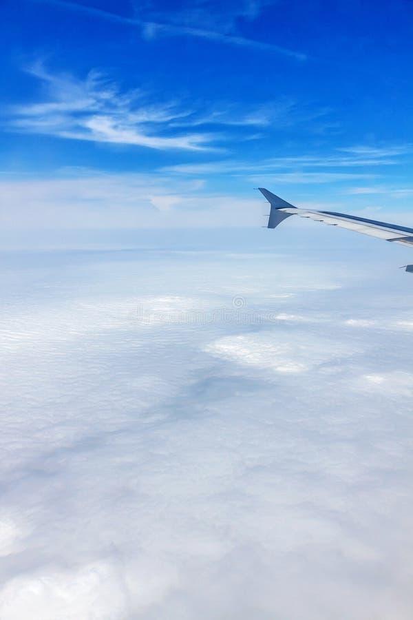 Volo dell'aeroplano - vista della finestra sopra le nuvole fotografia stock libera da diritti