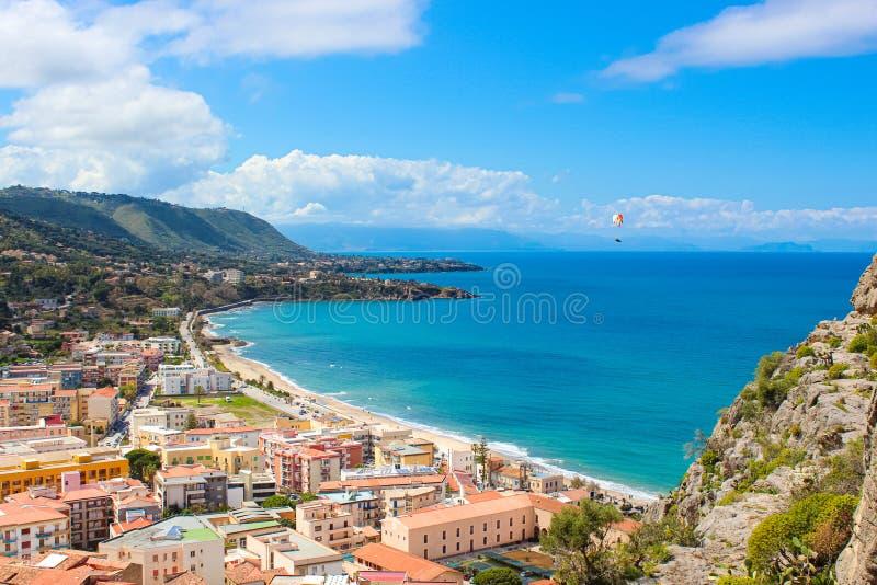 Volo dell'aliante sopra il paesaggio stupefacente della città costiera Cefalu in bella Sicilia Il parapendio è uno sport estremo  fotografie stock