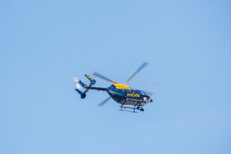 Volo dell'elicottero di polizia contro un chiaro cielo blu fotografia stock libera da diritti