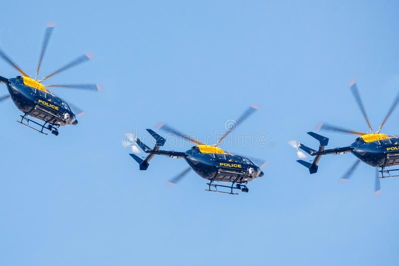 Volo dell'elicottero di tre polizie contro un chiaro cielo blu immagine stock
