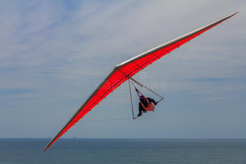 Volo dell'uomo di deltaplano su un'ala arancio a Funston forte in San fotografia stock libera da diritti