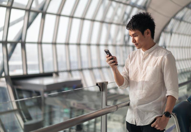Volo dell'uomo e Smart Phone aspettanti usando in aeroporto fotografie stock libere da diritti