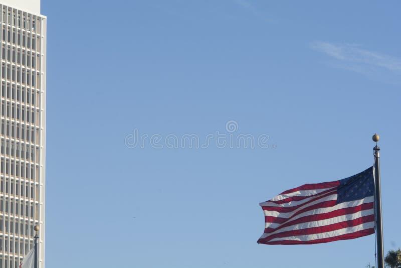Volo della bandiera americana nel vento con l'edificio per uffici nel fondo immagine stock libera da diritti
