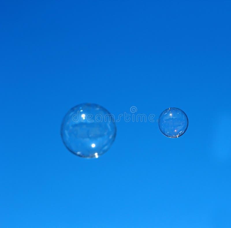 Volo della bolla di sapone contro il cielo blu immagini stock
