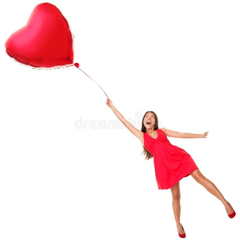 Volo della donna di giorno dei biglietti di S. Valentino con l'aerostato del cuore fotografie stock