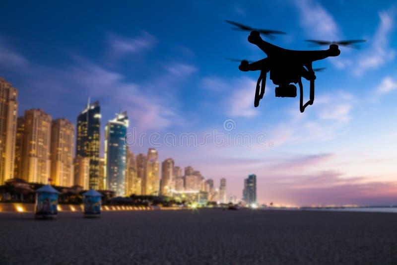 Volo della siluetta del fuco sopra il panorama della città del Dubai fotografie stock
