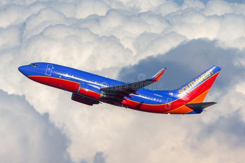 Volo di Southwest Airlines Boeing 737 dopo una grande formazione della nuvola fotografia stock