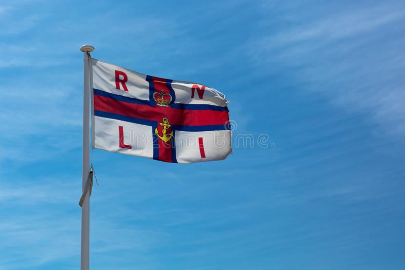 Volo nazionale reale della bandiera dell'istituzione RNLI della lancia di salvataggio sopra la stazione del bagnino in Southwould fotografia stock libera da diritti