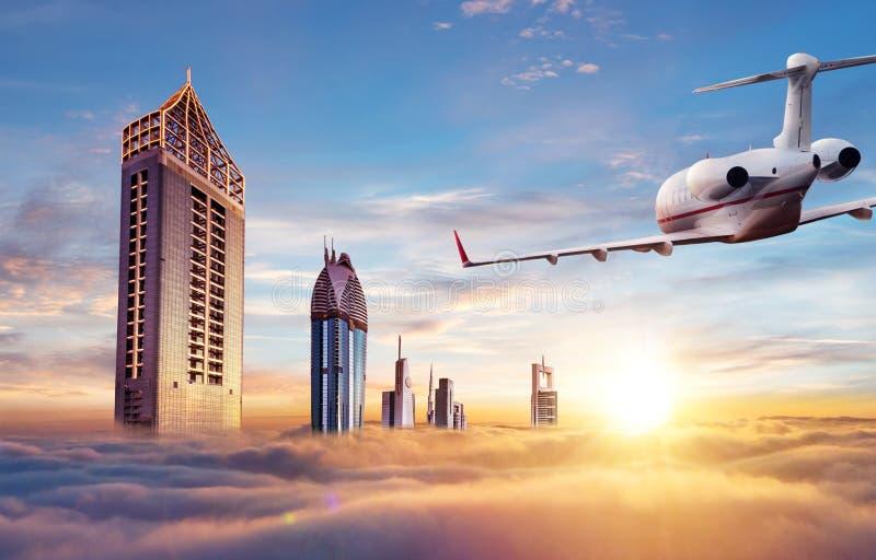 Volo privato dell'æreo a reazione sopra la città del Dubai fotografia stock
