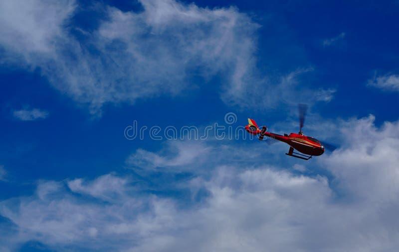 Volo rosso dell'elicottero con il cielo blu e le nuvole bianche nel fondo immagine stock libera da diritti