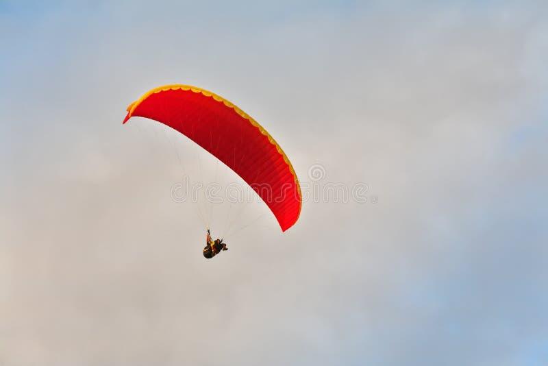 Volo sui paracadute su un tramonto immagine stock
