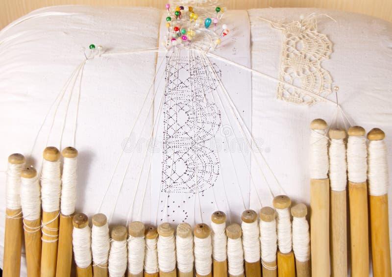 Vologda dimensionaal kant, vlasdraden, die op spoelen van kamperfoelie weven royalty-vrije stock afbeeldingen
