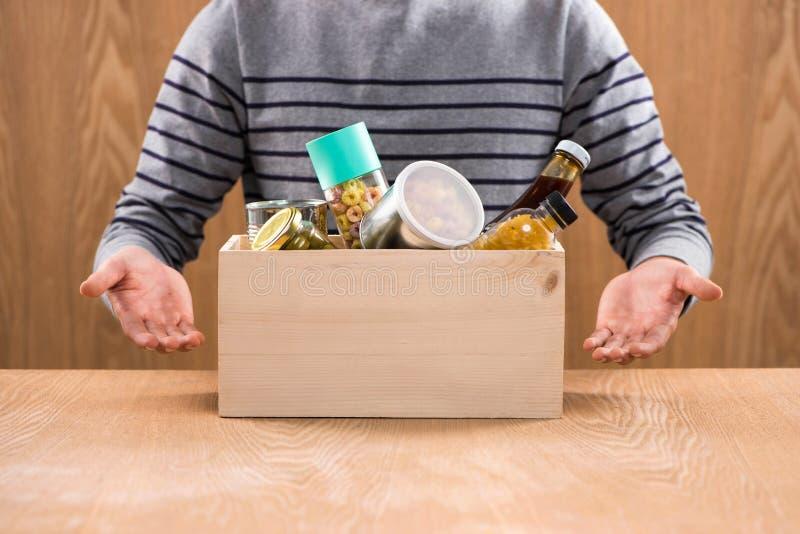 Volontär med donationasken med livsmedel på träbakgrund royaltyfri fotografi