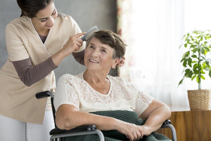 Volontär som kammar äldre tålmodigt hår för ` s royaltyfria bilder