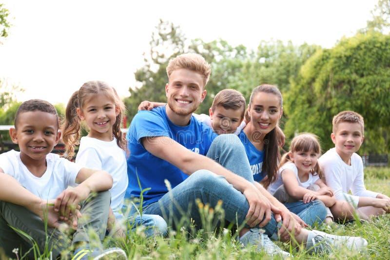 Volontärer och ungar som sitter på gräs royaltyfri fotografi