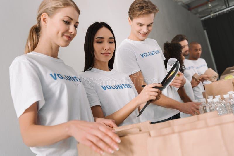Volontärer som packar mat för välgörenhet royaltyfri fotografi