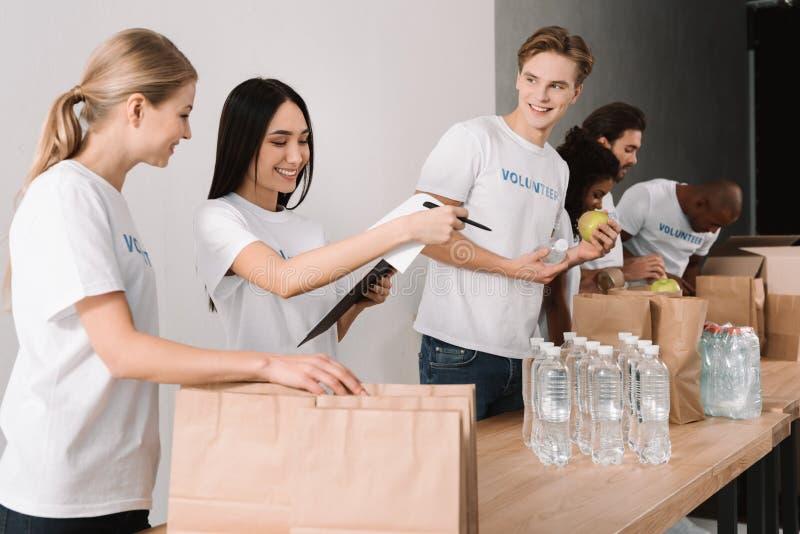 Volontärer som packar mat för välgörenhet royaltyfria bilder