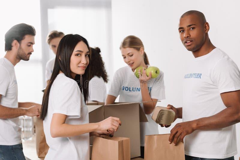 Volontärer som packar mat för välgörenhet royaltyfria foton