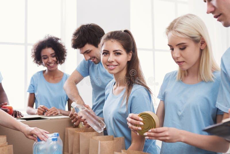 Volontärer som packar mat och drinkar in i pappers- påsar royaltyfri foto