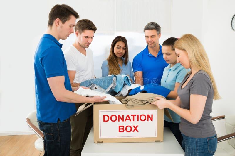 Volontärer som rymmer kläder för att donera royaltyfri foto