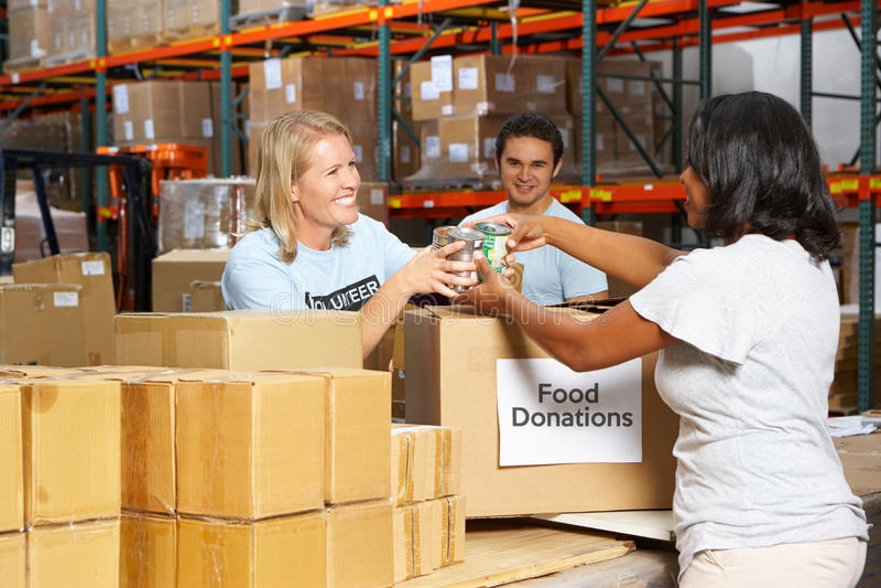 Volontärer som samlar matdonationer i lager arkivfoto