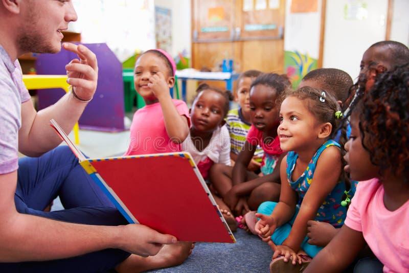 Volontärlärare som läser till en grupp av förskole- ungar royaltyfri foto