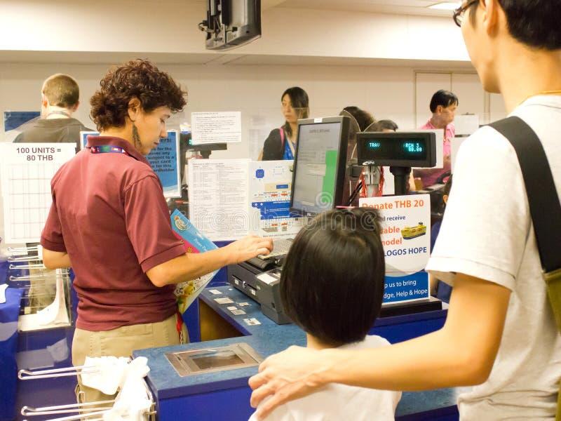 Volontaire avec des visiteurs au compteur de caissier. photographie stock libre de droits