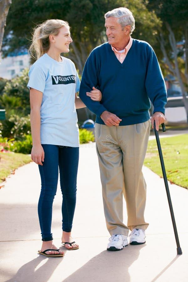 Volontaire d'adolescent aidant l'homme aîné ToWalk photos libres de droits