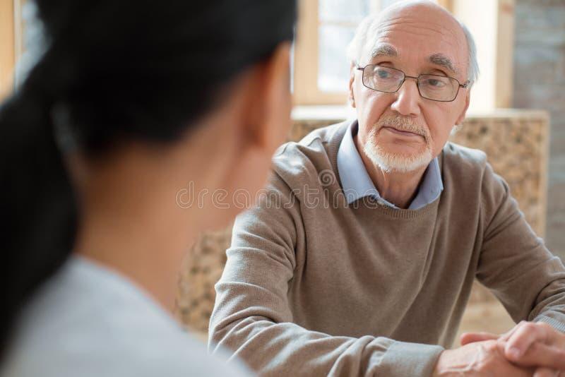 Volontaire et homme supérieur sérieux ayant la conversation images stock