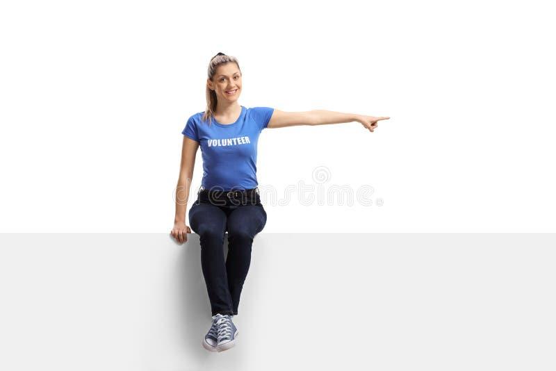 Volontaire féminin s'asseyant sur un panneau blanc et se dirigeant dans une direction images stock