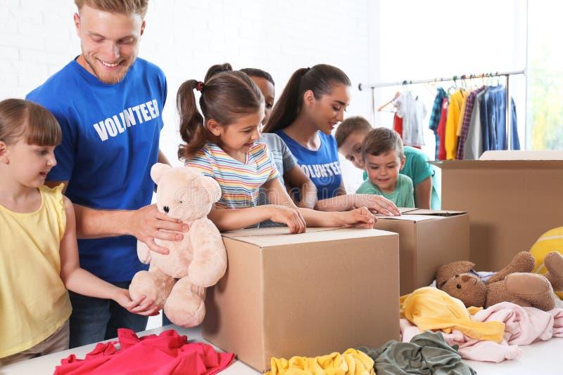Volontaires avec des enfants assortissant des marchandises de donation photo stock