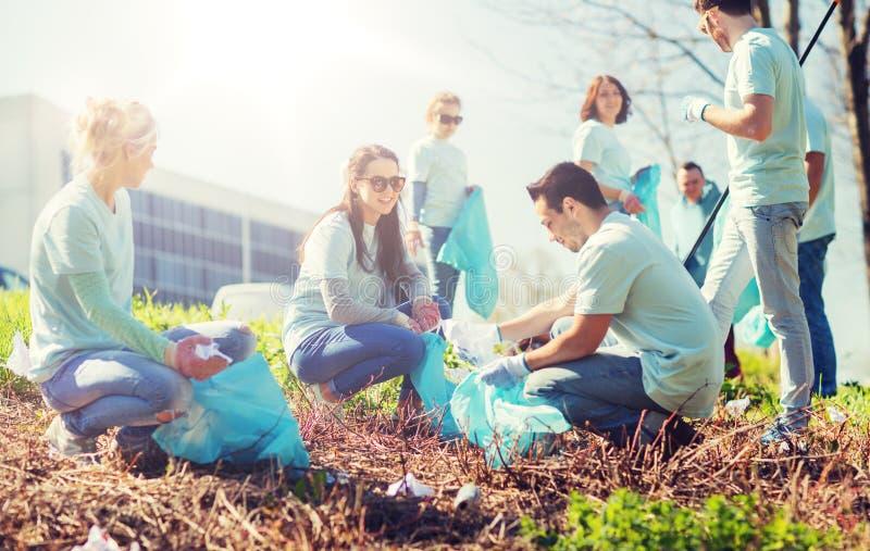 Volontaires avec des sacs de déchets nettoyant le secteur de parc image stock