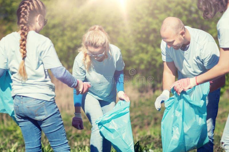 Volontaires avec des sacs de déchets nettoyant le secteur de parc photo stock