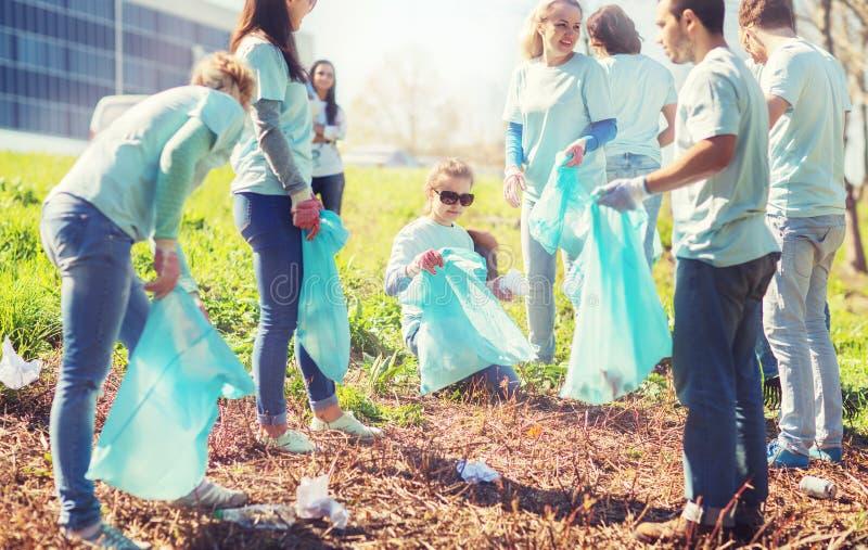 Volontaires avec des sacs de déchets nettoyant le secteur de parc photographie stock libre de droits