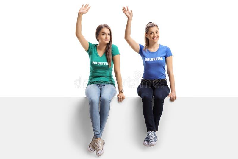 Volontaires de jeunes femmes s'asseyant sur un panneau et une ondulation blancs photos libres de droits